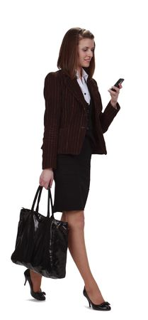 Young businesswoman checking her mobile phone while is walking,isolated against a white background. photo