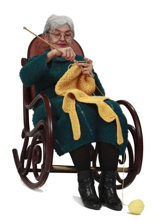 grizzled: Image of an old woman sitting on a rocker and knitting, isolated against a white background. Stock Photo