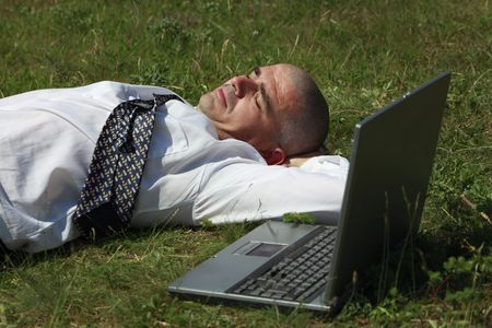 Tired man sleeping in a field near his laptop. photo