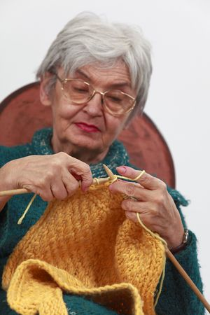 deftness: Image of an old woman knitting.Selective focus on the hands. Stock Photo