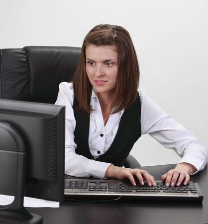 Young businesswoman at her desk working on the computer Stock Photo - 7060540