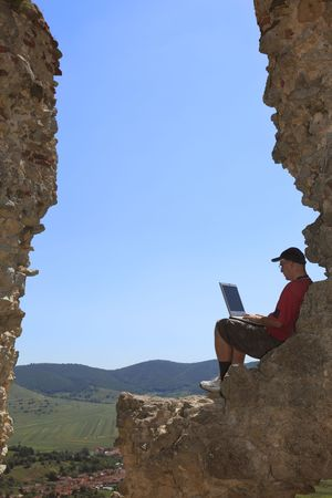 Image of a man working on a laptop outdoors. photo