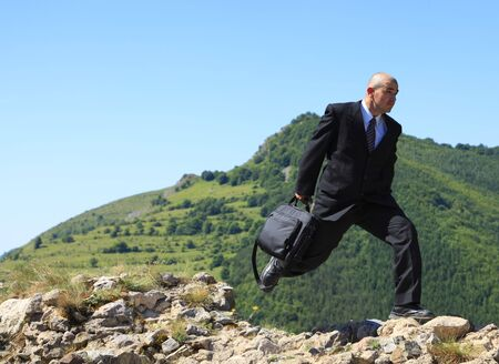Businessman with a laptop bag running outdoors on a rocky ruined stronghold wall in a mountaineous area.The image can suggest the idea of a thief stealing important data or a man protecting data in case of a disaster. photo