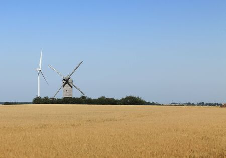 eolian: Image of a traditional windmill close to a modern eolian turbine in a cereal field. Stock Photo