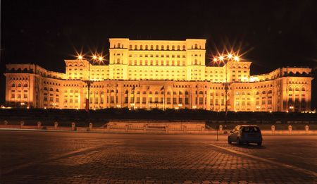 bucharest: Night image of a car in front of the The Palace of the Parliament, also known as The Peoples House in the Cheaucheskus era, in Bucharest,Romania. The Palace is the worlds largest civilian administrative building, The Pentagon being the largest overall. Stock Photo
