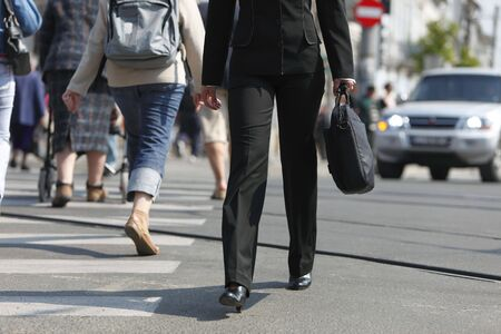 Image of a businesswoman's lower body. She is carrying a computer bag while crossing the street in a city.