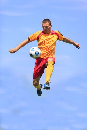 Soccer player kicking the ball while jumping. photo