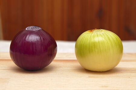 sameness: Image of two different onions on a kitchen table. Stock Photo