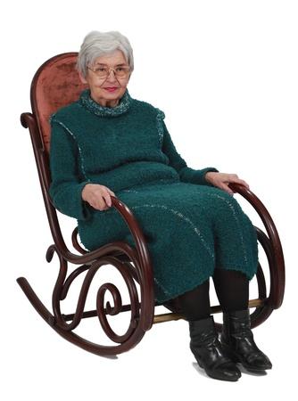 silla de madera: Mujer sentada en una mecedora de madera aislada sobre un fondo blanco.