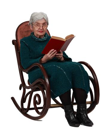 Old woman with a red book sitting in a rocker and looking to the camera, isolated against a white background. photo