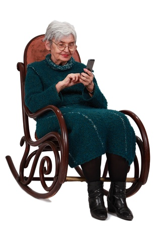 Image of a senior woman siting in a rocker and writing a phone message. photo
