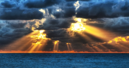 Dramatic sunset rays through a cloudy dark sky over the ocean. photo