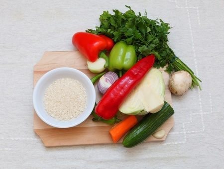 Upper view of various vegetables and a bowl of rice on a chopping board on a table. Stock Photo - 8667147