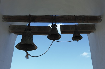summon: Image of bells in a belfry of a Moldavian monastery against the blue sky.