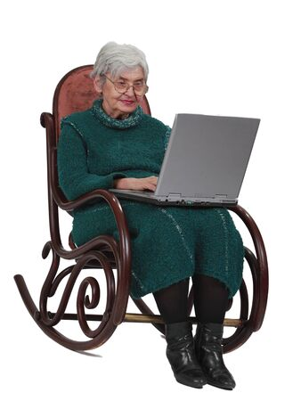 Image of a senior woman using a laptop while sitting in a rocker. Stock Photo