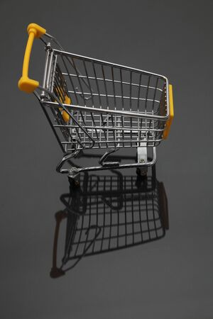 Image of an empty shopping cart and its shadows against a black background. photo