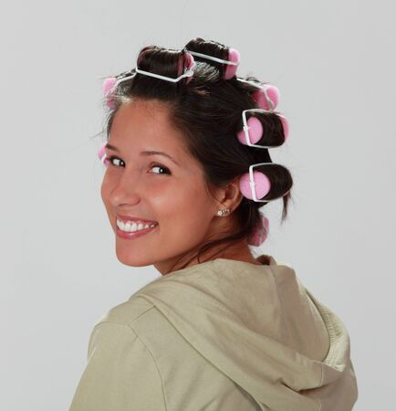 Porfile of a young woman with hair curlers on her head. photo