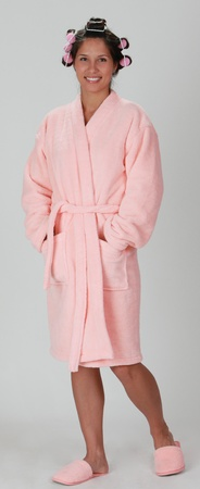 lady        slipper: Young woman in a pink plush bathrobe with curlers standing against a grey background.
