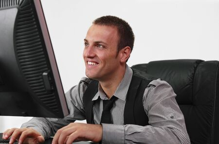 Smiling young businessman working on a computer on his desk. photo