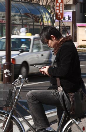 Sendai,Japan,February 26th 2007: A young Japanese boy checking his mobile phone while on bicycle in Sendai streets.Sendai is the capital city in Miyagi Prefecture in Japan and the biggest city in Tohoku Region. On 11 March 2011, a 9.0 earthquake and a sub
