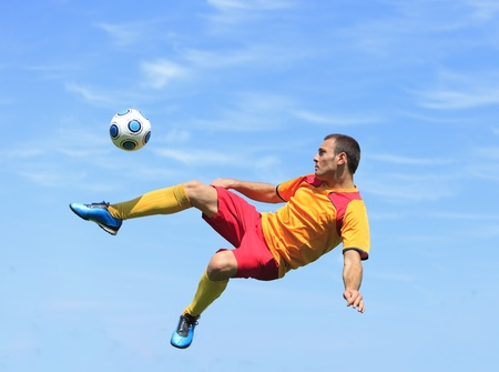 A soccer player kicking the ball in an acrobatic position.