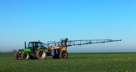 A tractor spreading substances in the early spring in a field in Central region of France.