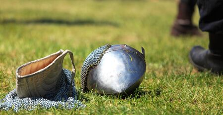 templars: Image of a steel helmet and a chainmail hood on a filed after a medieval fight in a sunny day.