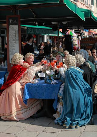 Venice,Italy,February 26th,2011:A group of people wearing traditional medieval Venetian costumes celebrating on a street terrace in Venice during the Carnival days.The Carnival of Venice (