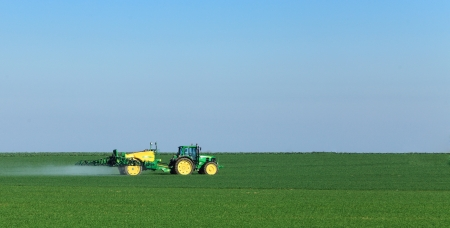 Blandainville,France,March 21st,2011:A tractor spreading substances in the early spring in a field in Central region of France.