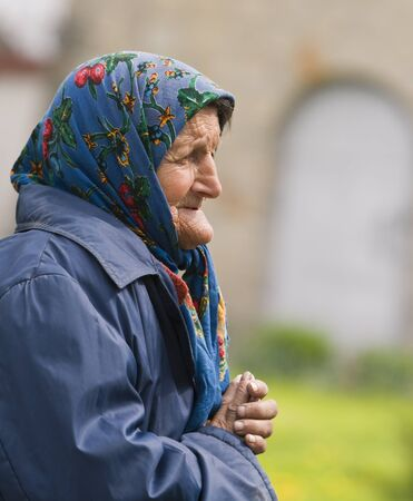 Bacau,Romania,April 20th 2008:Portrait of an old poor woman praying. Stock Photo - 9232309
