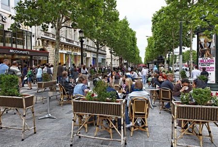 cafeterias: Paris,France,June 12th 2010:Crowded terrace on the Avenue des Champs-�lys�es during a cloudy afternoon.