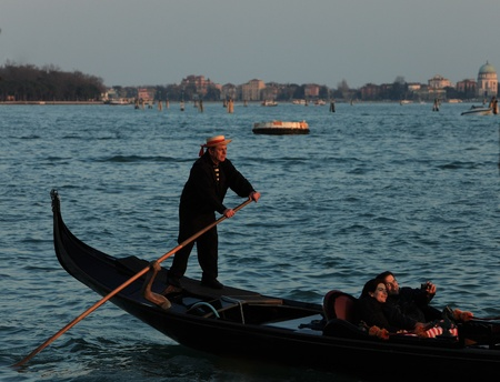 Venice,Italy,February 25th 2011: A young couple shoot a romantic self portrait using a prosumer digital camera while they are in a gondola steered by an old gondolier in a warmy twilight.
