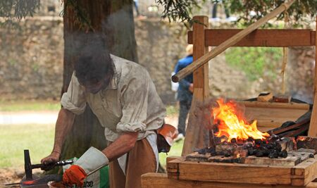 medieval blacksmith: Nogent le Rotrou,France,May 15th 2010: Image of a medieval blacksmith working in smoke near the fire during the �Week-end de L�ascension-Grand F�te m�di�vale�. This was a historical reenactment festival around the Saint Jean Castle.