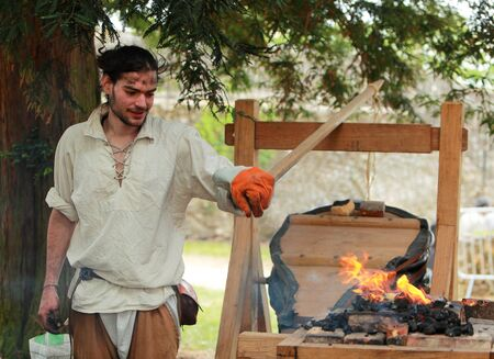 medieval blacksmith: Nogent le Rotrou,France,May 15th 2010: Image of a medieval blacksmith using a big fire rake during the �Week-end de L�ascension-Grand F�te m�di�vale�. This was a historical reenactment festival around the Saint Jean Castle.