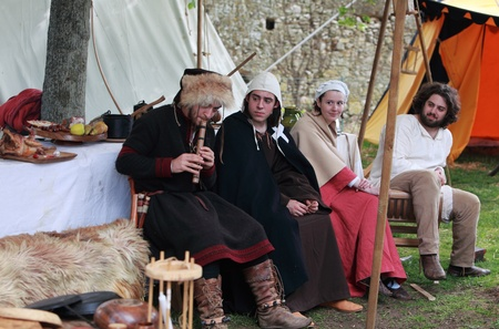 templars: Nogent le Rotrou,France,May,16th,2010:A group of four medieval teenagers listening a pipe song in front of their traditional tents during the Week-end de Lascension-Grand Fete medievale. This was a historical reenactment festival around the Saint Jean Ca