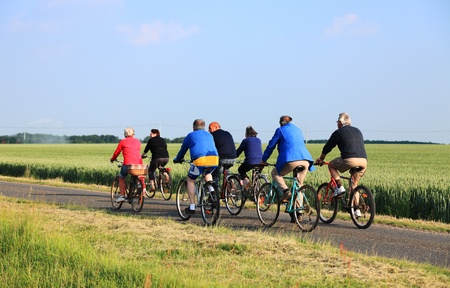 Blandainville, June 2nd 2010: A group of senior people riding their bicycles on a lane between wheat fields in Centre region of France.Riding bicycles is a very common activity in France which is the home of the most famous bicycle race in the world-Tour  Stock Photo - 9433688