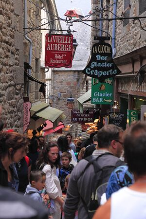 Mont Saint Michel,France,July 16th 2010: Image of crowd of tourists in a narrow street full of shops and restaurants near the Mont Saint Michel Monastery in Base Normandy,France.Mont Saint Michel Monastery is one of the first three most visited place in F