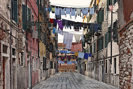 Traditional Italian street with clothes hanging out to dry between old houses, somewhere in Venice. Stock Photo