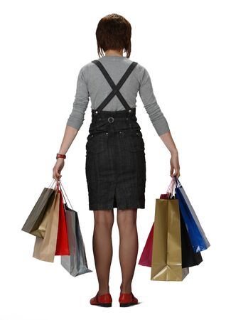 Rear view of a young woman holding shopping bags isolated against a white background. photo