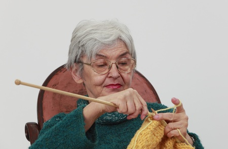 Portrait of an old woman knitting,against a gray background. photo
