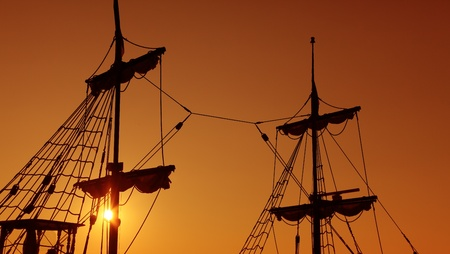 suggesting: Silhouettes of old-fashioned masts against a twilight sky suggesting idea of navigation Stock Photo
