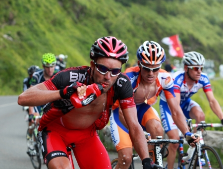 Beost,France,July 15th 2011: The  cyclist George Hincapie (BMC racing team ) drinking water while he climbs the category H mountain pass Abisque in the 13th stage of the 2011 edition of Le Tour de France, the biggest cycling race in the world. Such plasti Stock Photo - 10499999