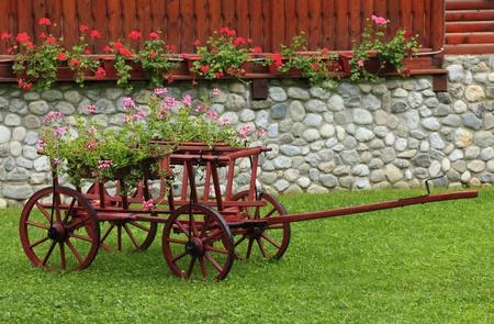 carreta madera: Agradable y colorido jardín con una carreta de madera. Foto de archivo