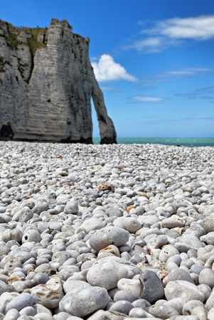 Image of the rocky beach and iconic natural arch from Etretat in Upper Normandy in North of France. Selective focus on the rocks in the first plane. photo
