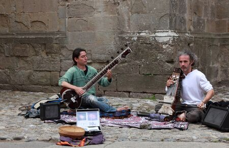 Carcassonne, France, July 17th 2011:Two men playing traditional Indian instrumets in the streets of the Fortified town of Carcassonne in France.The man from the left plays sitar and that from the right plays sarangi which is an Indian fiddle.