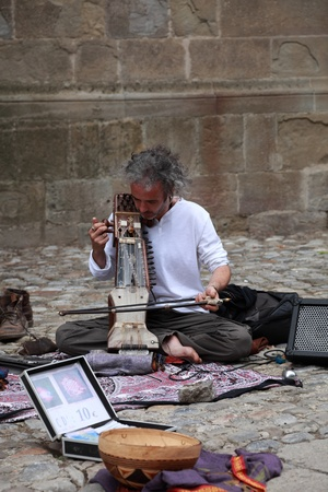 Carcassonne,France,July 17th 2011: Down in the streets of the fortified town of Carcassonne from France a man plays a traditional Indian instrument called sarangi which is in fact an Indian Fiddle.