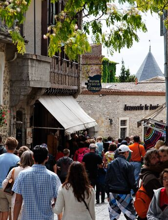 fortify: Carcassonne,France,July 17th 2011:  Image of crowd of tourists in a commercial street in the fortified city of Carcassonne in Aude department of France.The historic city of Carcassonne is an excellent example of a medieval fortified town whose massive def