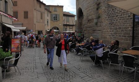 Carcassonne,France,July 17th 2011: Image of people waliking in a street with many terraces in the fortified city of Carcassonne in Aude department of France.The historic city of Carcassonne is an excellent example of a medieval fortified town whose massiv