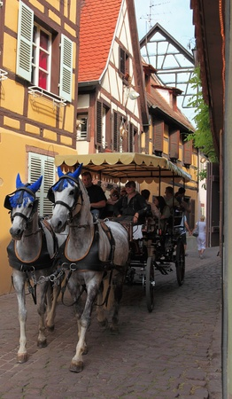 colmar: Colmar,France,April 23th 2011: Image of a two horse-drawn carriage passing by on a narrow traditional street in Colmar in Alsace in north-eastern France. The streets of Colmar are full of traditional Alsatian houses.The city is considered the