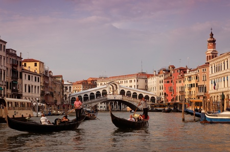 rialto bridge: Venice,Italy,July 29th 2011: Gondoliers sailing on Grand Canal in front of the Rialto Bridge in Venice.Venice is a special city in Italy,built in an archipelago of 117 islands formed by 177 canals in a shallow lagoon, connected by 409 bridges. In the old